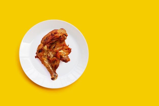Frango frito em chapa branca sobre fundo amarelo.