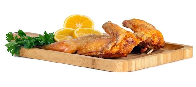 Frango frito em uma borda de madeira com salsa e limão no branco. comida.
