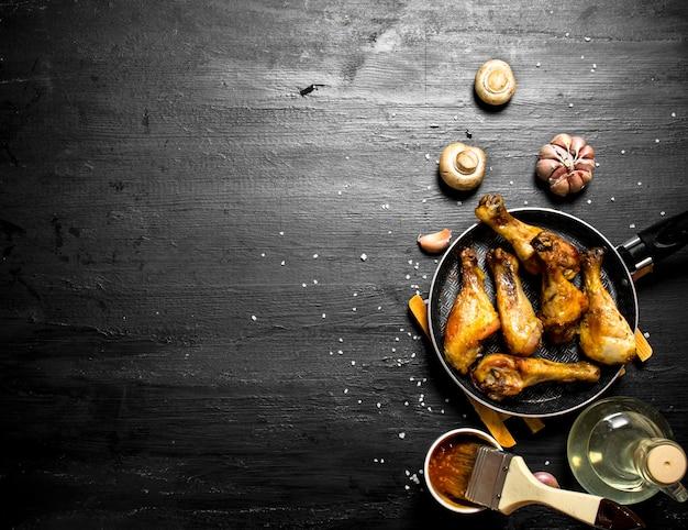 Frango frito em uma panela com cogumelos, alho e molho de tomate