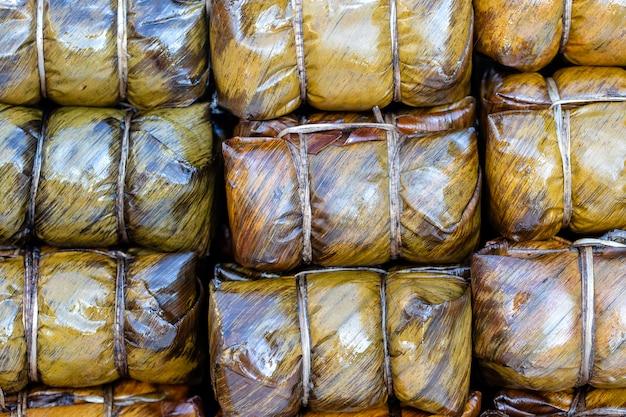 Frango frito embrulhado em folhas verdes de pandan no mercado de comida de rua na tailândia, close-up. conceito de comida tailandesa