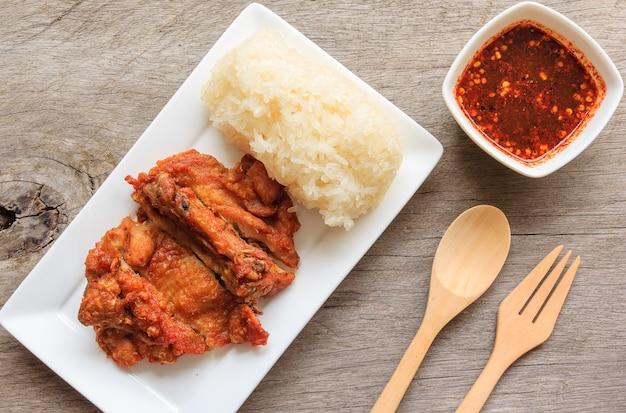 Frango frito estilo tailandês com molho picante vermelho e arroz isolado na mesa de madeira