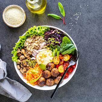 Frango grelhado, arroz, grão de bico picante, abacate, repolho, pimenta tigela buddha na superfície escura, vista superior. conceito de comida balanceada deliciosa