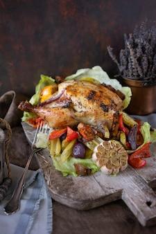 Frango grelhado caseiro com legumes e ervas na placa de madeira vintage