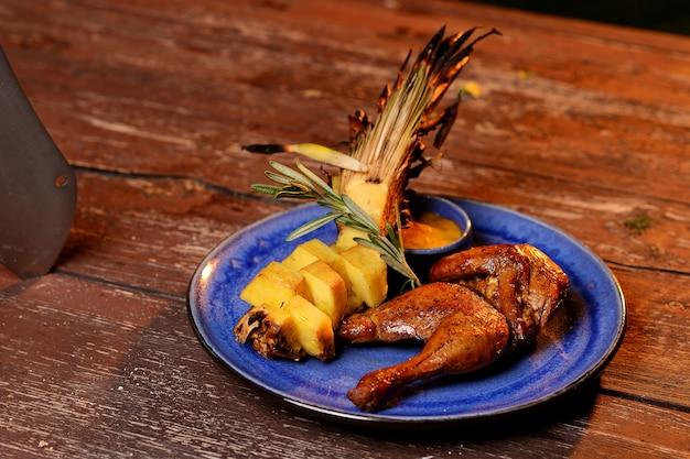 Frango grelhado com abacaxi e molho. em uma placa azul em uma mesa de madeira