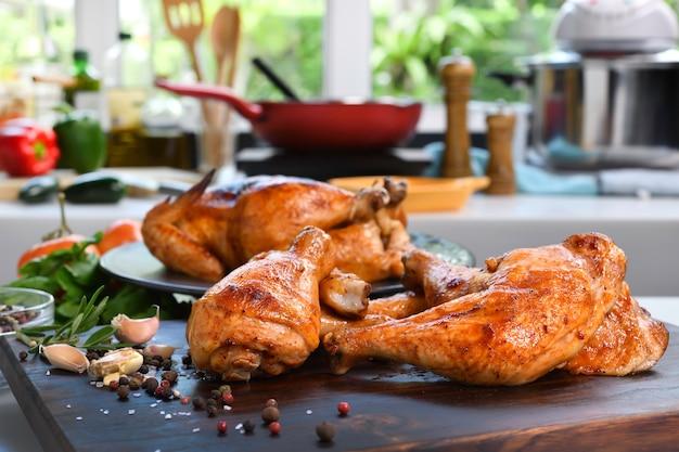 Frango grelhado com ingrediente em uma tábua de madeira na cozinha