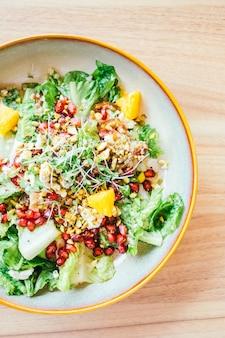 Frango grelhado com legumes e romã, salada de frutas no prato