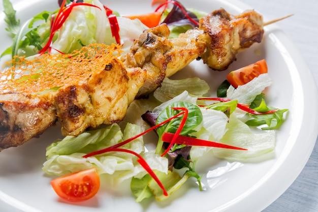 Frango grelhado de carne no palito com salada e tomate em chapa branca