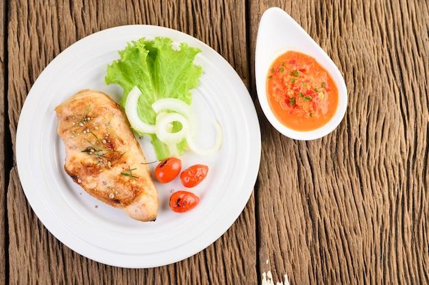 Frango grelhado em um prato branco com tomate, salada, cebola, pimenta e molho.