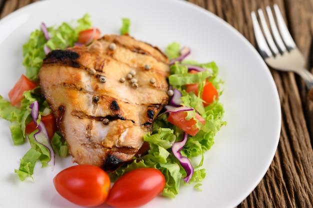 Frango grelhado em um prato branco com uma salada de tomate, cenoura e pimentão cortado em pedaços.
