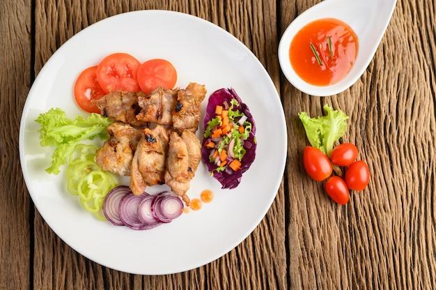 Frango grelhado em um prato branco com uma salada, tomate, pimentão cortado em pedaços e molho na mesa de madeira.