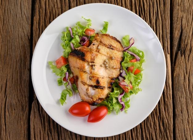 Frango grelhado em um prato branco com uma salada, tomate, pimentão cortado em pedaços na mesa de madeira.