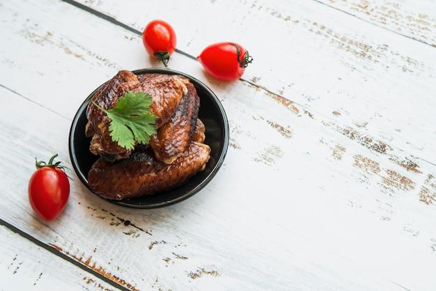 Frango grelhado saudável na tigela com tomate na mesa de madeira