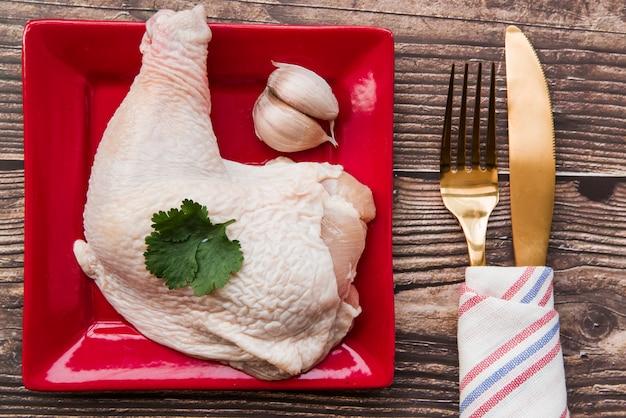 Frango guarnecido no prato com garfo e faca de manteiga na mesa de madeira