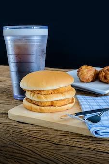 Frango hambúrguer e frango frito, copo de coca-cola na tábua de madeira com faca e garfo