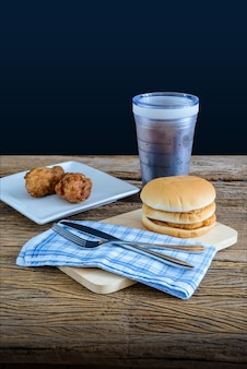 Frango hambúrguer e frango frito, copo de coca-cola na tábua de madeira com faca, para