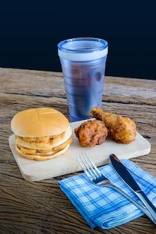 Frango hambúrguer e frango frito, copo de coca-cola na tábua de madeira com faca