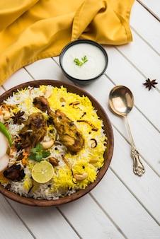 Frango hyderabadi ou dum biryani, servido em um kadhai ou tigela com molho de iogurte. foco seletivo