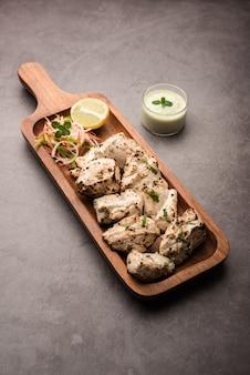 Frango indiano afegão malai tikka é um kabab cremoso murgh grelhado servido com salada fresca