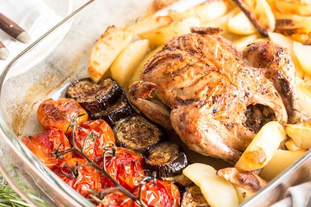 Frango inteiro assado com batatas, berinjela e tomate cereja. jantar saudável