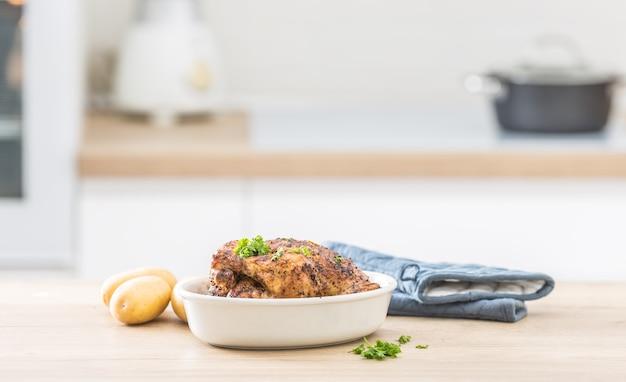 Frango inteiro assado no prato branco com batatas cruas na mesa cozinhada. interior da casa em segundo plano.