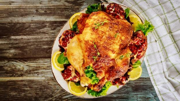 Frango inteiro assado no prato com salada e romã.
