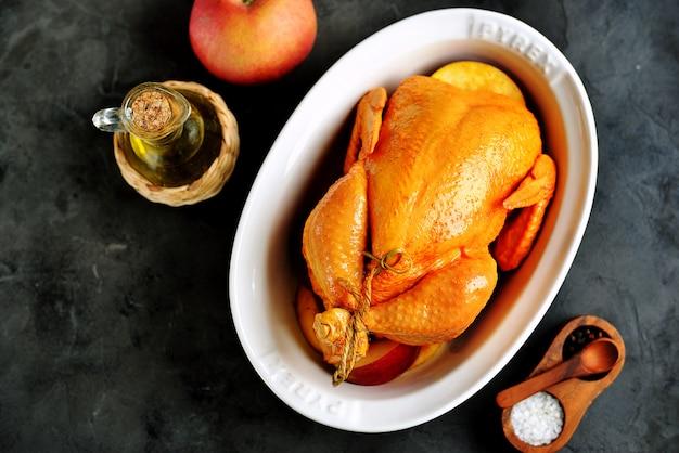 Frango inteiro cru marinado em azeite, molho de soja, vinagre de vinho branco com açafrão, tomilho e fatias de maçã. vista do topo.