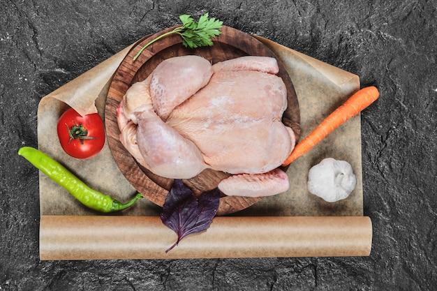 Frango inteiro cru no prato de madeira com legumes frescos