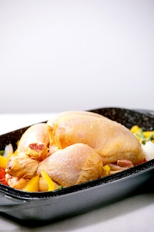 Frango inteiro cru orgânico cru com pimentão de legumes fatiado, cebola e ervas na bandeja do forno, pronto para cozinhar. mesa de mármore branco. copie o espaço