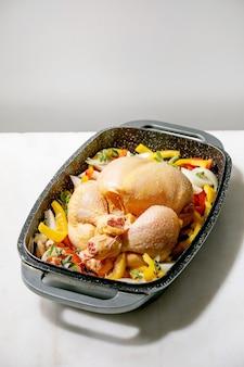 Frango inteiro cru orgânico cru com pimentão de legumes fatiado, cebola e ervas na bandeja do forno, pronto para cozinhar. mesa de mármore branco.