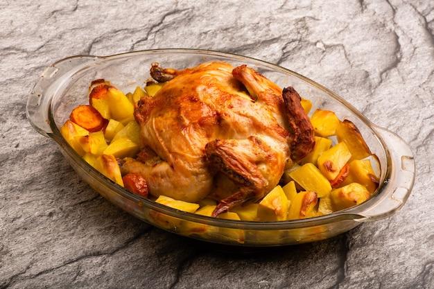Frango inteiro grelhado caseiro com batata assada na mesa