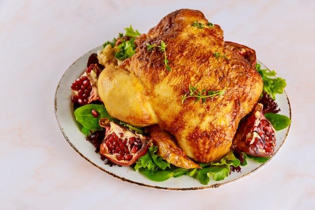 Frango inteiro grelhado no prato com salada verde e romã.