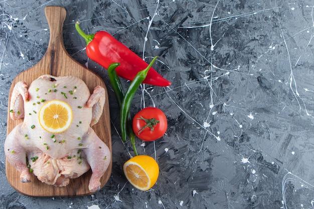 Frango inteiro marinado cru em uma tábua ao lado de vegetais, no fundo de mármore.