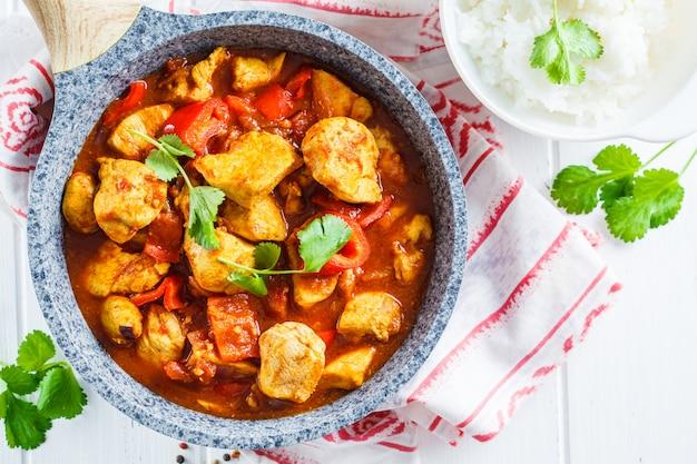 Frango jalfrezi na frigideira com uma tigela de arroz, vista superior, copie o espaço. conceito de cozinha tradicional indiana.