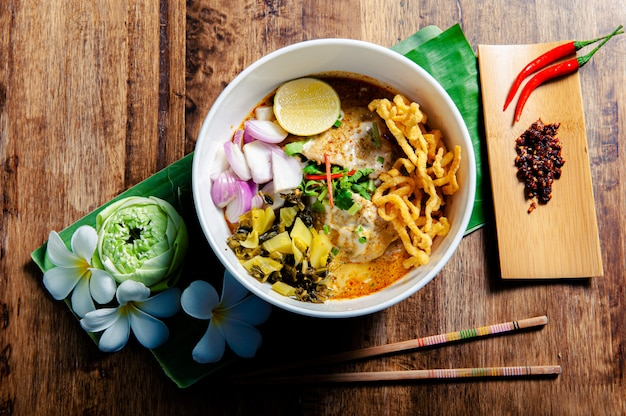Frango khao soi, um alimento tailandês amplamente popular no norte, junto com os acompanhamentos.