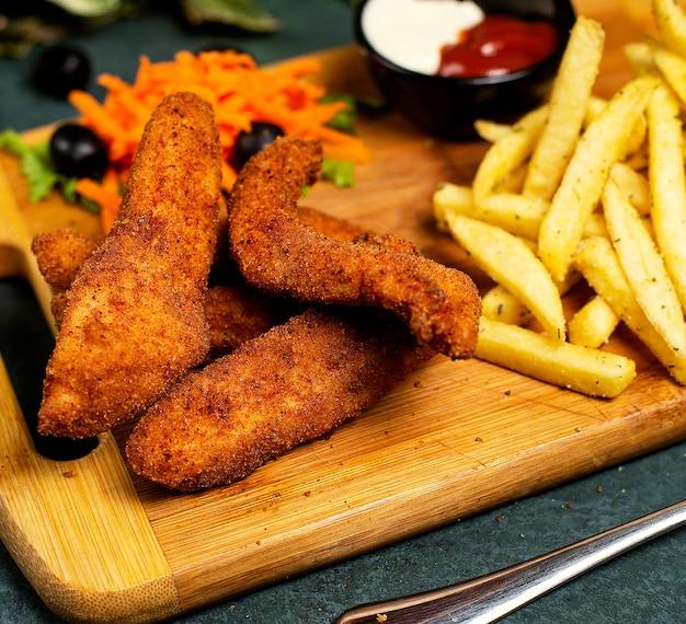 Frango nuggets estilo kfc com batatas fritas, maionese, ketchup e salada de legumes