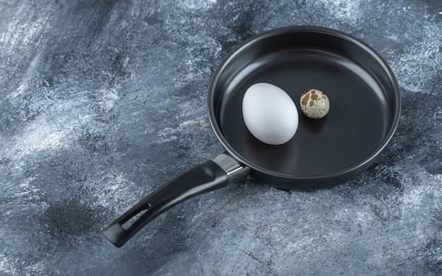 Frango orgânico fresco e ovos de codorna na frigideira preta.