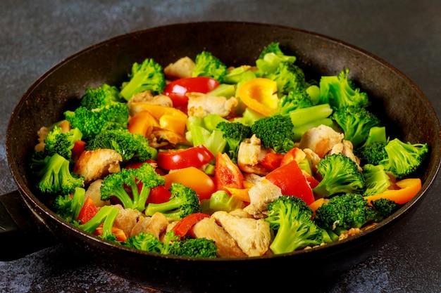 Frango prato asiático com páprica e brócolis no wok