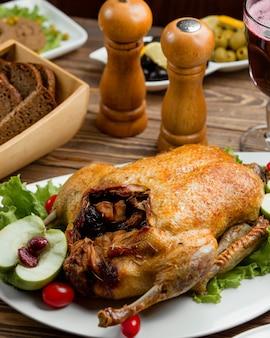 Frango recheado inteiro assado, servido com pão e vinho tinto