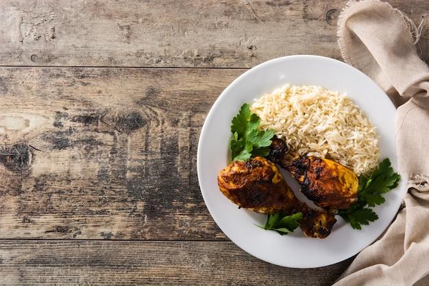 Frango tandoori assado com arroz basmati no prato na mesa de madeira. vista superior.