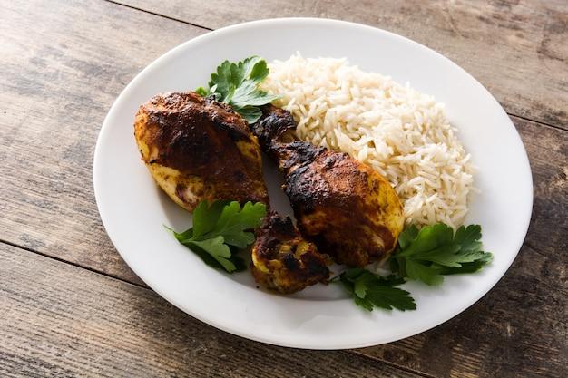 Frango tandoori assado com arroz basmati no prato na mesa de madeira.
