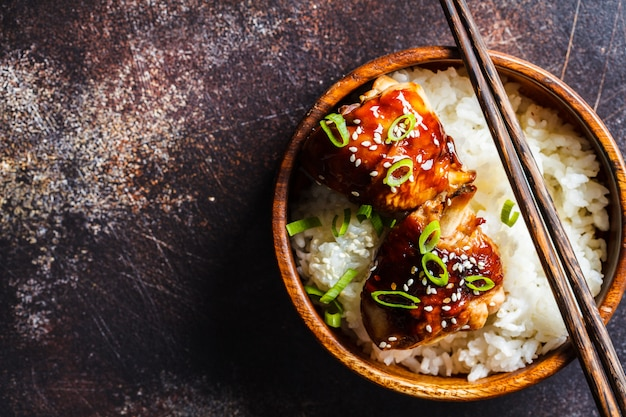 Frango teriyaki com arroz branco em uma tigela de madeira.
