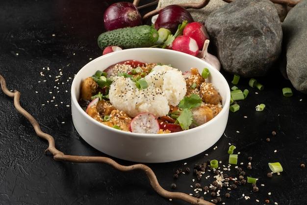 Frango teriyaki com arroz e vegetais. um prato principal quente asiático com aves, arroz cozido, cebolas, rabanetes, ervas e sementes de gergelim