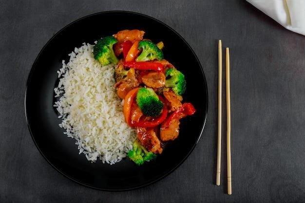 Frango teriyaki e brócolis frite com foco seletivo de arroz