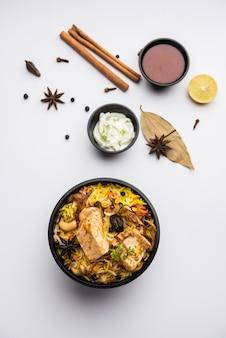 Frango tikka biryani estilo restaurante embalado para entrega em domicílio em caixa de plástico ou recipiente com raita e salan