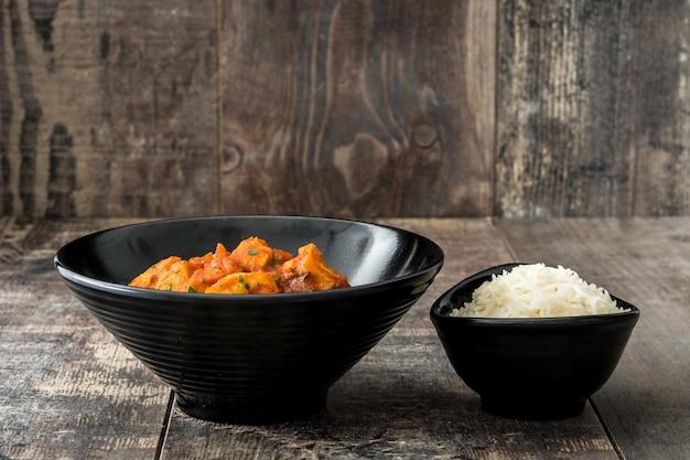 Frango tikka masala com arroz basmati em tigela preta na mesa de madeira