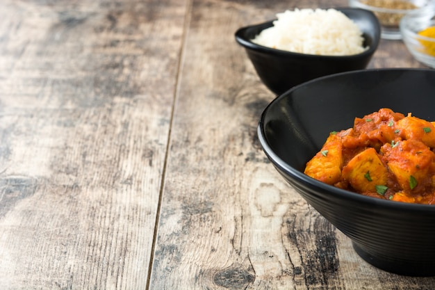 Frango tikka masala com arroz basmati em tigela preta no espaço da cópia de mesa de madeira