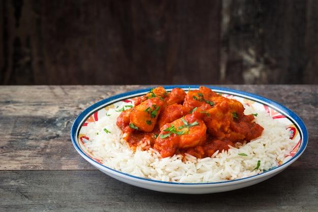 Frango tikka masala com arroz basmati na mesa de madeira