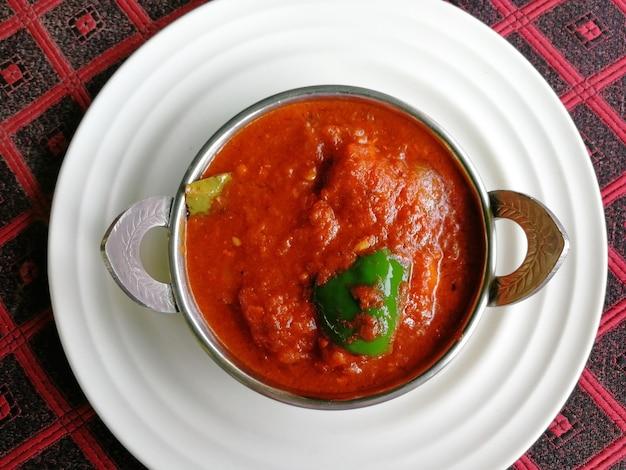 Frango tikka masala em kadai em um prato branco. delicioso prato indiano picante. vista superior, configuração plana