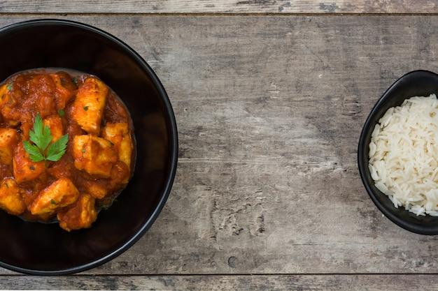 Frango tikka masala em tigela na vista superior de mesa de madeira