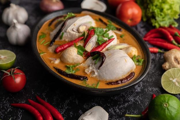 Frango tom yum com pimenta, coentro, pimenta seca, folhas de limão kaffir, cogumelos e capim-limão em uma tigela